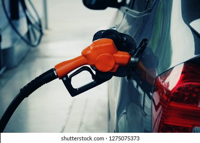 close up orange nozzle fuel fill oil into car tank at pump gas station, transport energy, transportation power business technology concept, vintage tone