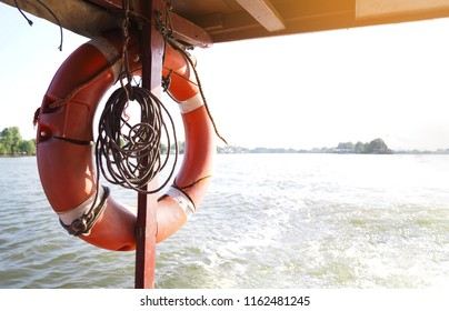 Close up orange old lifebuoy hanging at wooden pole in the ship running on the river. Local travelling in Thailand.