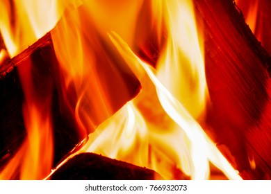close up of orange and red flames burning on a fire with logs