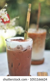 Close up organic iced chocolate and iced latte with reed straw ( rye grass or bamboo straw) and flower and tree background.
