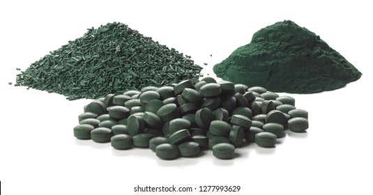 Close up of organic spirulina tablets, flakes and powder over white background.