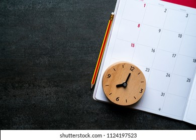close up of organizer or calendar, clock and pencil on the black table, planning for business meeting or travel planning concept