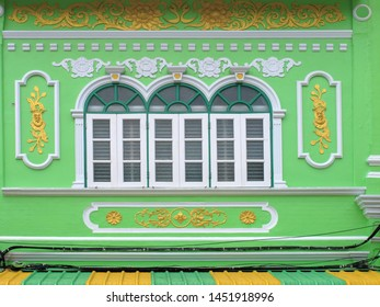 close up ornate exterior of green color government building with windows in Bangkok, Thailand
