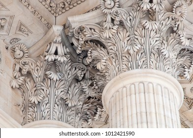 A close up of ornate leaf design at the top of fluted Corinthian columns.