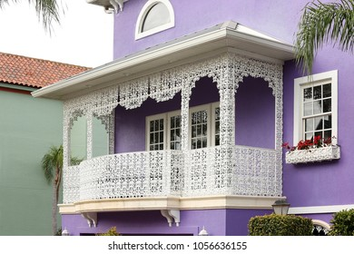 Close up of an ornate white metal balcony in front of a purple house.