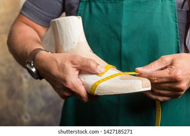 close up of orthopedic shoemaker measuring a wooden last