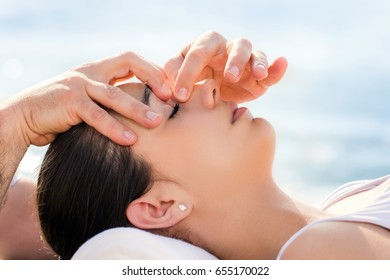 Close up of osteopath doing facial therapy on woman outdoors.Therapist applying pressure with fingers between eyes.