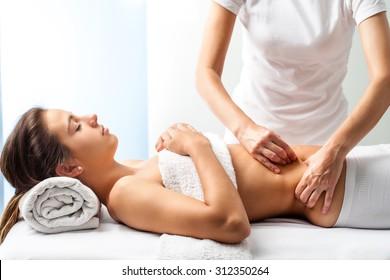 Close up of osteopath doing manipulative massage on female abdomen.
