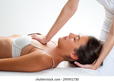 Close up of osteopath doing thorax manipulation massage on young woman.One hand doing physical force on chest and on hand behind head.