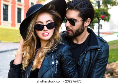 Close up outdoor fashion portrait of stylish young pretty couple in love hugs on the street of old town, wearing stylish total black leather rock n roll clothes ,sunglasses and hat.