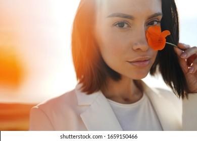 Nahaufnahme eines Outdoor-Lifestyle-Porträts von schöner junger Frau mit Mohnblume in der Hand. Freiheit und Unabhängigkeit.Weiche Farben.
