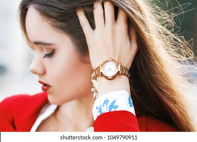 Close up outdoor photo of stylish golden wrist watch on the woman`s hand. Selective focus. Fashion details