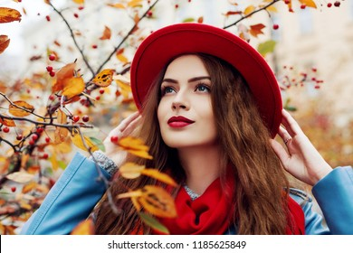 Close up outdoor portrait of young beautiful happy smiling girl wearing red hat and scarf posing near autumn tree. Model with red lips, long hair. Lady looking up.