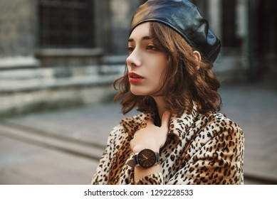 Close up outdoor portrait of young fashionable woman wearing leather beret, black wrist watch, leopard print coat. Copy, empty space for text