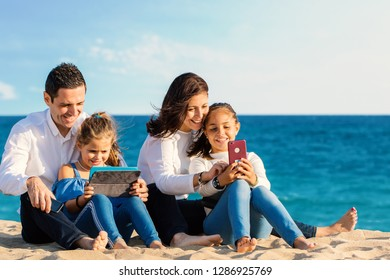 Close up outdoor portrait of young parents sitting with kids on beach. Family looking and laughing together at digital tablet and smartphone.