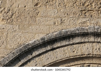 Close up outdoor view of an ancient stone arche. Architectural element of an old church in France. Grey textured stone lighted by rhe sun. Pattern with circular lines. Abstract architectural image.