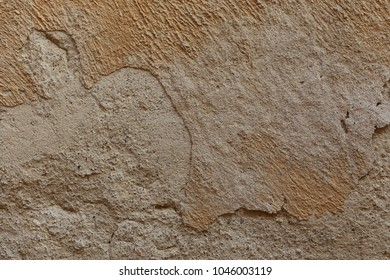 Close up outdoor view of a clear brown decrepite painted wall of an ancient house. Rough surface with different shapes traces. Aged and weathered facade detail. Abstact textured image.