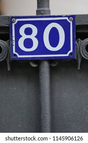 Close up outdoor view of the number eighty written in white on a blue rectangular metallic plate. Sign 80 to indicate the address of a house in France. Isolated numerical element place on a gate.