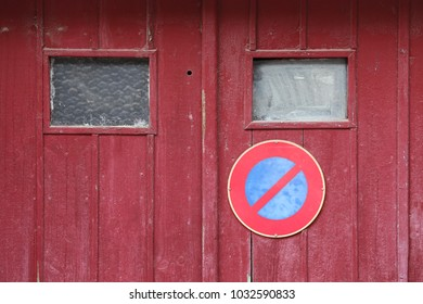 Close up outdoor view of an old wooden garage door with the symbol no parking. Small windows, purple planks with the circular sign in blue and red. Rough vintage texture. Abstract architectural image.