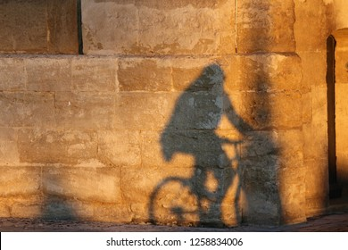Close up outdoor view of the shadow of a cyclist projected on an ancient stone wall. Silhouette of a person cycling drawn on a textured lighted surface. Bicycle on an urban facade in a french city.
