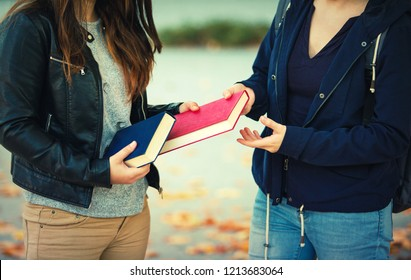 Close up outdoors portrait of two women students exchanging books. Knowledge sharing between people. Give to read to a friend.
