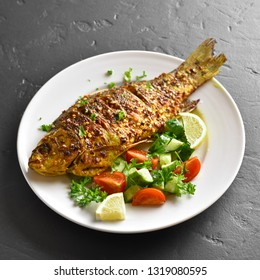 Close up of oven baked fish on plate over black stone background. Healthy seafood. Tasty cooked fish salad from fresh vegetables (cucumber, tomato, greens).