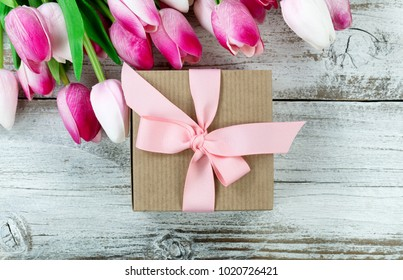 Close up overhead view of a brown gift box with pink tulips in background on white weathered wooden boards