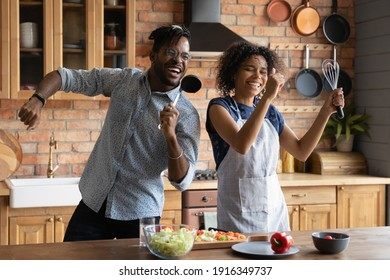Close up overjoyed African American couple singing into kitchenware, having fun, dancing, listening to music in kitchen, cooking salad, excited wife and husband holding whisk and ladle a microphone