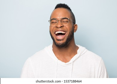 Close up of overjoyed african American millennial man in glasses isolated on blue studio background feel euphoric laugh loud, excited happy biracial male have fun smile at joke, humor concept
