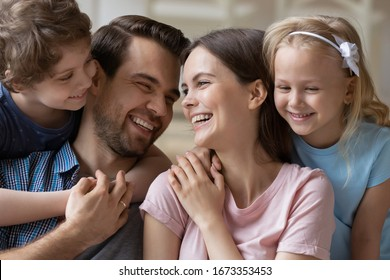 Close up of overjoyed young parents hug cuddle with smiling little kids have fun laughing spending weekend at home, happy family with small children siblings embrace enjoy leisure time together
