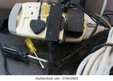 Close up overloaded and dusty multi plug and electric power cables. Electrical Safety Concept.