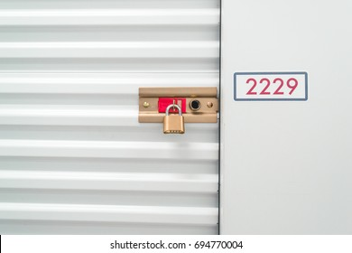 Close up of a pad lock and red number on a white storage unit.