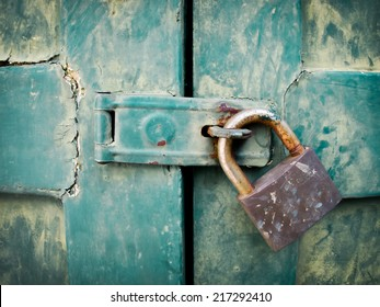 Close up of padlock and old metal hasp and staple on an vintage wooden door
