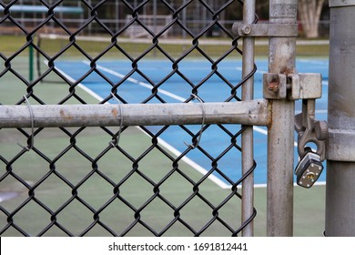 Close up of the padlocked gate of a tennis court with net in background.