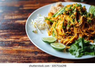 Close up Padthai noodle with smoke tofu and mixed vegetable - wheat germs,lime,cucumber,parsley on wooden textured table.Healthy Vegetarian vegan menu