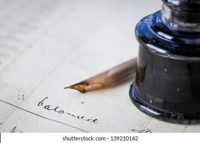 Close up of a page out of an antique accounting ledger with an old feather quill pen and an antique glass inkwell