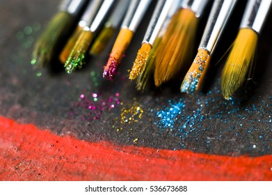 Close up of paint brushes cover with glitter sparkle, golden, magenta, blue, green colors, on rustic, wooden table background, glitter spread of, space for text, selective focus