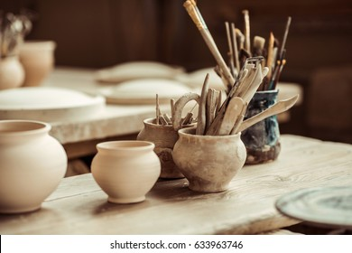 Close up of paint brushes with pottery tools in bowls on table