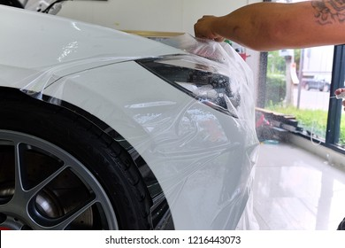 Close up of paint protection film installation on side mirror of modern luxury car. PPF is polyurethane film applied to painted of car to protect the paint from stone chips, bug splatter, and abrasion