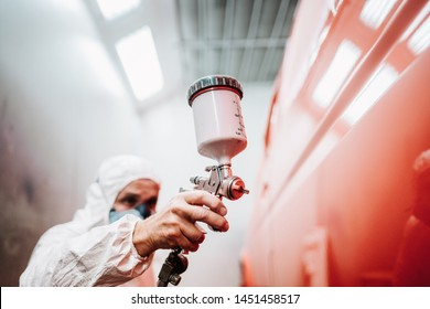 close up of paint spray gun, worker painting a car