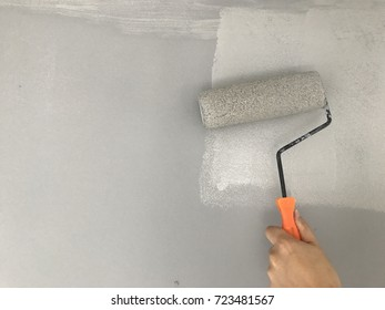 Close up of painter hand painting a wall with paint roller color background gray, copy space.
