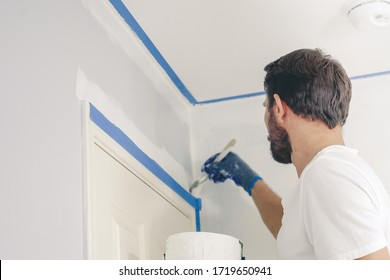 Close up of painter hands with gloves painting the wall edge by door frame.