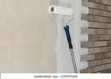 Close up of painter i'm painting a wall with paint roller.