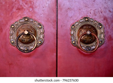 Close up of a pair of ancient Chinese brass door knockers on red lacquer wooden doors as vintage background