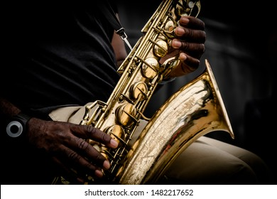 A close up of a pair of hands holding a saxophone.