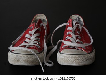 Close up of pair of sneakers - red and white vintage worn out shoes - youth hipster shoes on black background