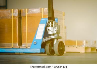 Close up pallet-jack wheel at a warehouse.