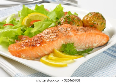 close up of pan fried salmon fillet served with roasted potatoes and fresh vegetables on white square plate
