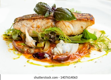 close up of a pan seared grill seabass fish fillet italian  livornese sauce with tomato, olives, capers, dill, oregano, chilly, clams , parsley, onion , basil, in a white plate , natural light