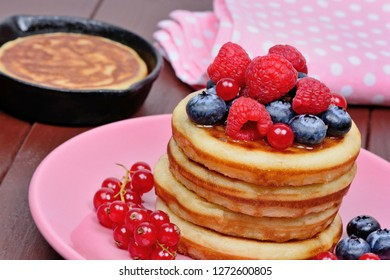 Close up of pancakes with fresh berries and orange juice
